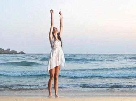 Γυναίκα σε παραλία με φόντο τη θάλασσα με λευκό φόρεμα και τα χέρια ψηλά