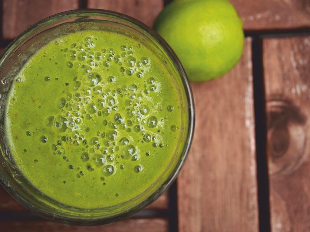 Ποτήρι με πράσινο smoothie κι ένα lime πάνω σε ξύλινο τραπέζι
