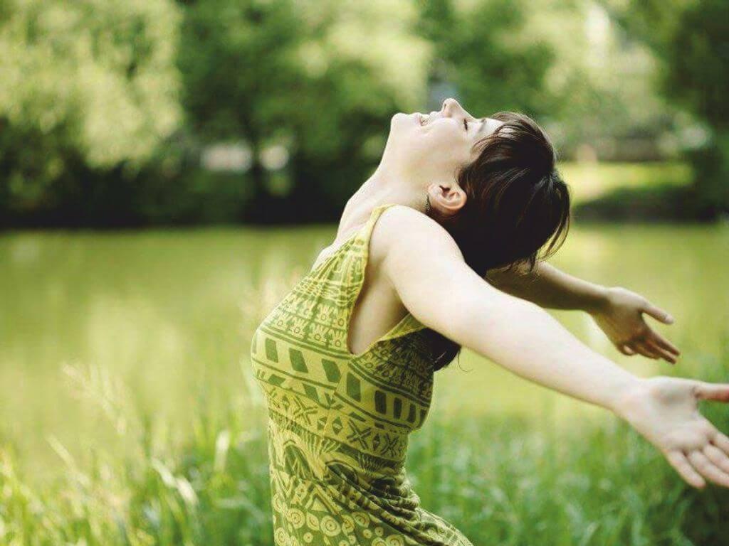 Γυναίκα με μαύρα μαλλιά και πράσινη μπλούζα χαμογελάει και έχει ανοιχτά τα χέρια της προς τα πίσω