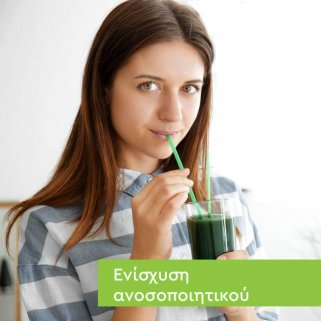 Κοπέλα με μακριά μαλλιά και ριγέ μπλουζάκι που πίνει πράσινο smoothie με Spiroulina platensis