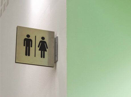 Τοίχος σε λευκό και πράσινο χρώμα με πινακίδα τουαλέτας που απεικονίζει με σκίτσο μια γυναικεία και μια ανδρική φιγούρα