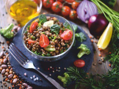 Μπολ με φακές σαλάτα γαρνιρισμένη με κομμένα ντοματίνια με φόντο κομμένα λαχανικά και ένα ποτήρι λάδι