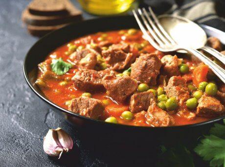 Μαύρο πιάτο με κομμάτια από μοσχάρι κοκκινιστό και αρακά