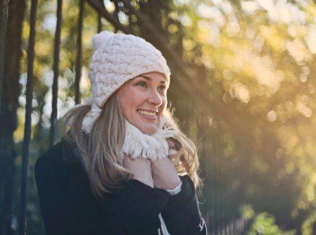 Γυναίκα με ξανθά μαλλιά που φοράει λευκό σκουφί και κασκόλ το κρατάει και χαμογελάει μέσα σ' ένα δάσος