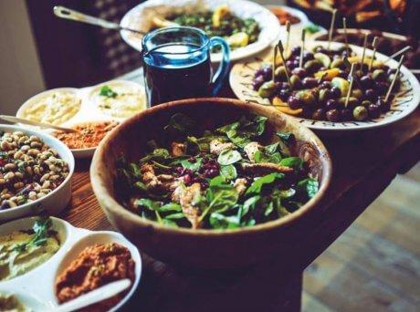 Τραπέζι με διάφορα πιάτα, στο κέντρο υπάρχει μία πράσινη σαλάτα, δίπλα ένα πιάτο με ελιές, πίσω κι άλλες σαλάτες