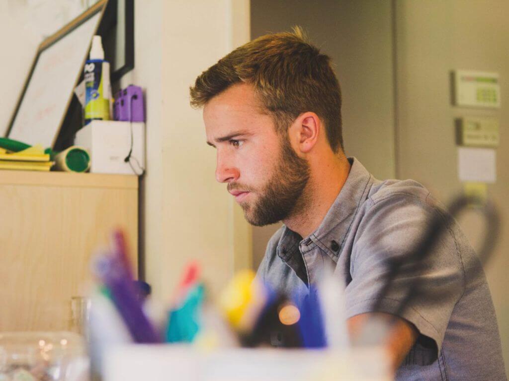 Νεαρός άνδρας με γένια διαβάζει σε ένα γραφείο