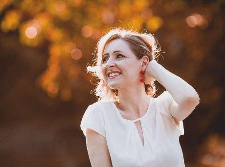 Ώριμη γυναίκα με λευκή μπλούζα φοράει κόκκινο κρεμαστό σκουλαρίκι, αγγίζει τα μαλλιά της και χαμογελάει