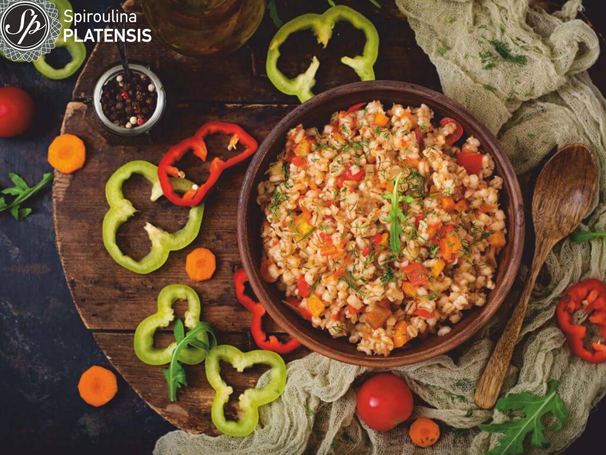 Ξύλινο πιάτο με κριθαράκι και κομμένα πολύχρωμα λαχανικά μέσα σ' αυτό πάνω σε έναν ξύλινο πάγκο με κομμένες κόκκινες και πράσινες πιπεριές, καρότα και ντοματάκια.