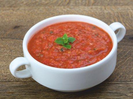 Λευκό μπολ με ντοματόσουπα γαρνιρισμένη με λαχανικά στο κέντρο