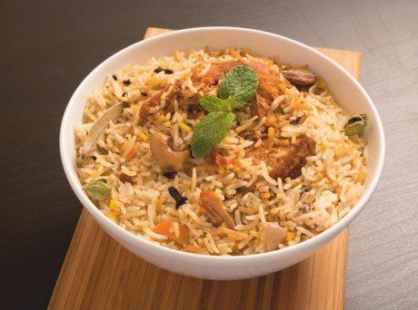 Λευκό μπωλ με ρύζι με κοτόπουλο, λαχανικά και Σπιρουλίνα flakes πάνω σε ξύλινο πάγκο