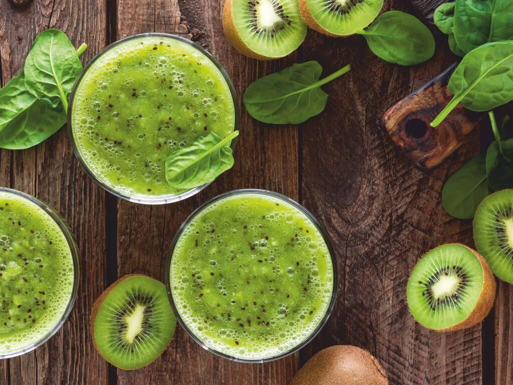 Δύο ποτήρια με πράσινο smoothie πάνω σε έναν ξύλινο πάγκο κοπής και γύρω τους φύλλα από σπανάκι και ακτινίδια