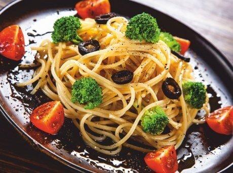 Μακαρόνια με μπρόκολο, ντοματίνια, ροδέλες ελιάς και Σπιρουλίνα flakes σερβιρισμένα σε καφέ πιάτο