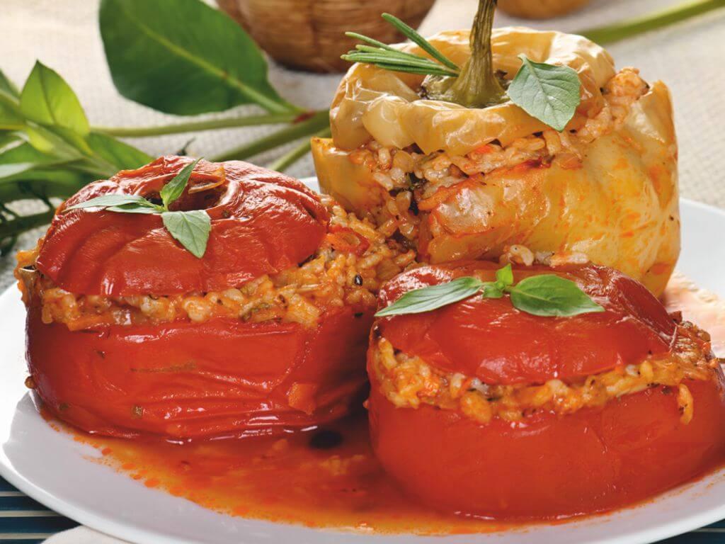 Πιάτο με δύο ντομάτες και μία πιπεριά πράσινη γεμισμένα με ρύζι και τραχανά