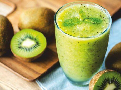 Ποτήρι με πράσινο smoothie με ακτινίδιο και Spiroulina PLATENSIS γύρω γύρω ακτινίδια ολόκληρα και κομμένα