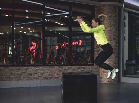 Γυναίκα με κίτρινη ζακέτα και μαύρο κολάν αθλείται πηδώντας από έναν μαύρο κύβο πάνω σε έναν άλλο