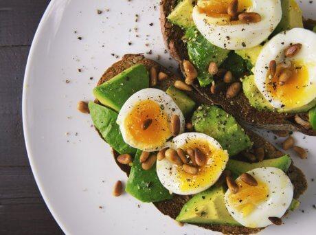 Πιάτο με ανοιχτό τοστ με αβοκάντο, αυγό και Σπιρουλίνα flakes