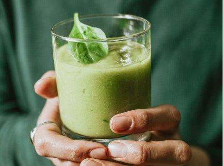 Ποτήρι με πράσινο smoothie με ένα φύλλο δυόσμο
