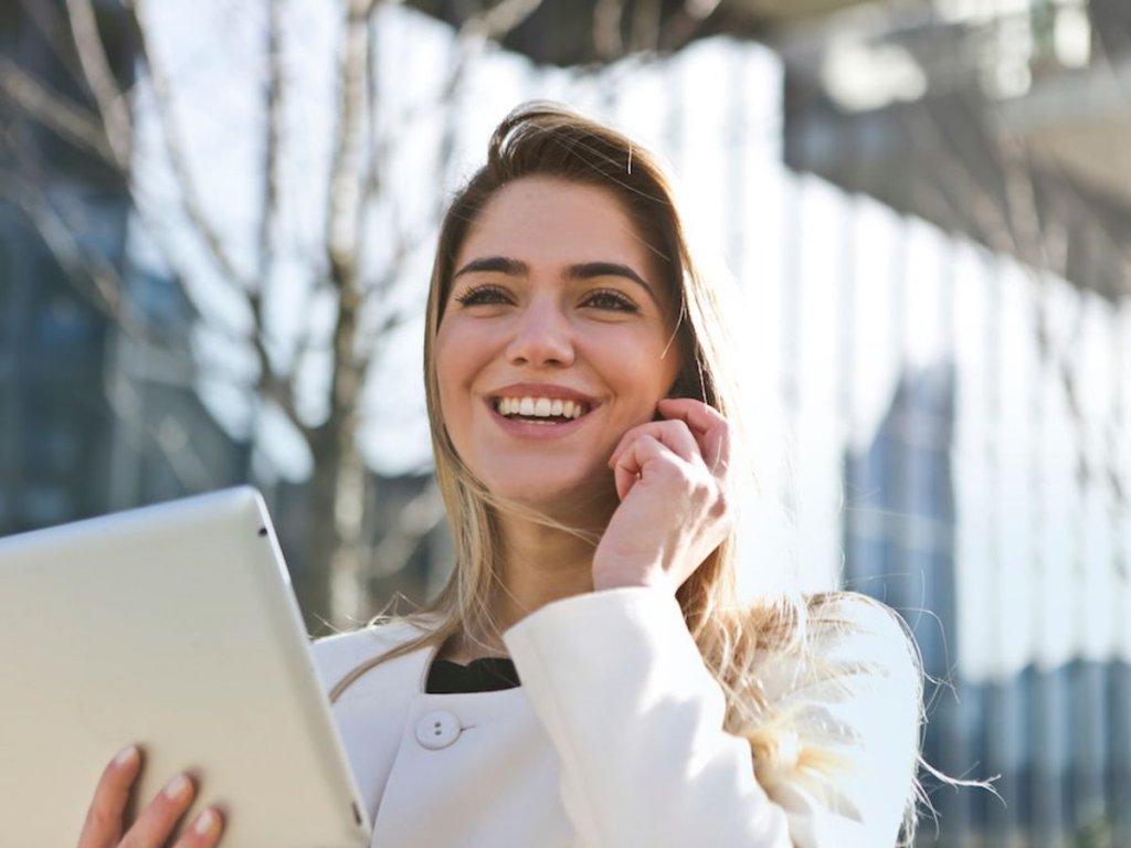 Χαμογελαστή ξανθιά γυναίκα μιλάει στο κινητό κρατώντας ένα tablet στο χέρι