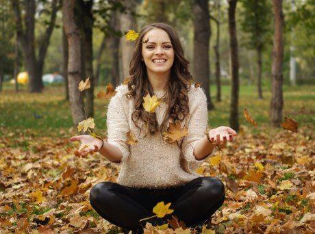Χαμογελαστή γυναίκα καθισμένη σε ένα πάρκο με ανοιχτά τα χέρια της και φύλλα που πέφτουν