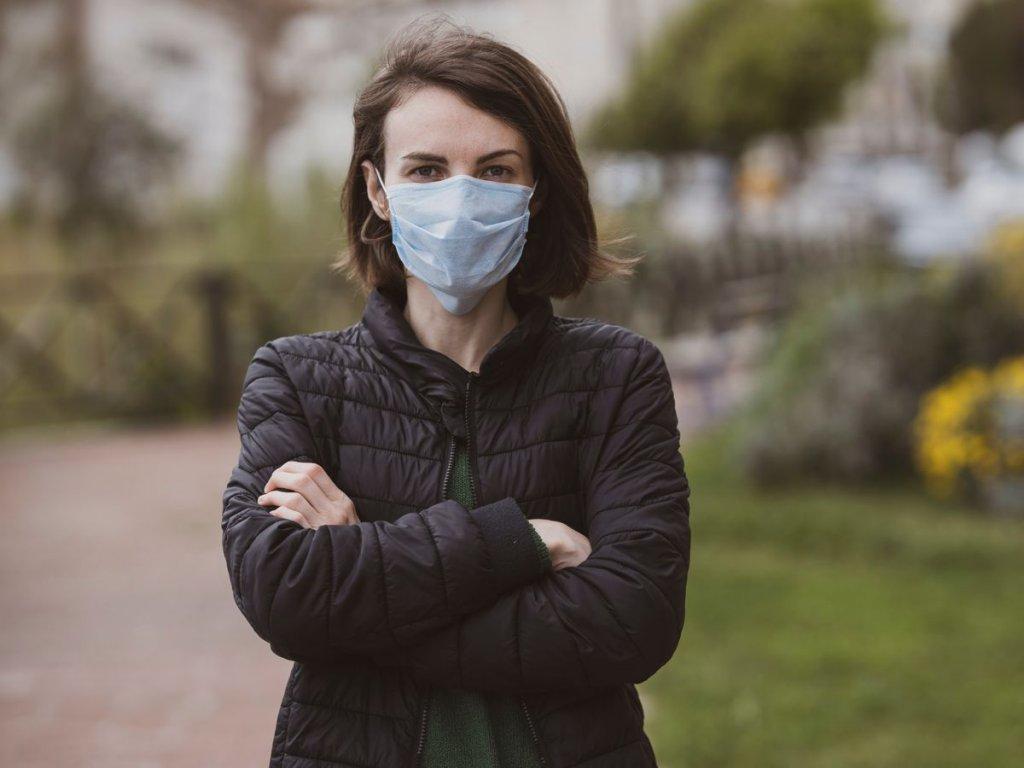 Γυναίκα με καστανά μαλλιά φοράει χειρουργική μάσκα σε εξωτερικό χώρο