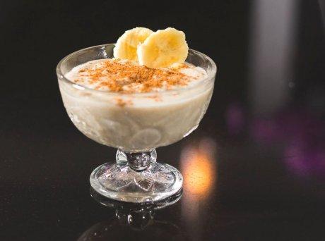Ποτήρι με ρυζόγαλο γαρνιρισμένο με κανέλα σε σκόνη και δύο μικρές φέτες μπανάνα