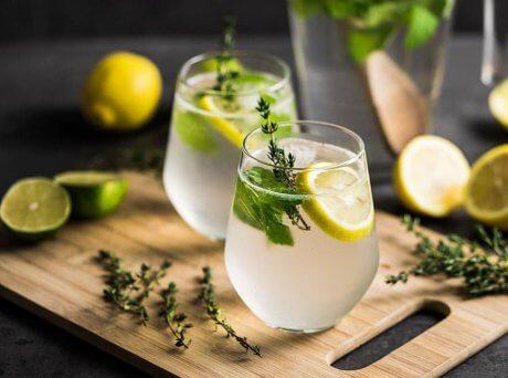 Δύο ποτήρια με λεμονάδα πάνω σε ξύλο κοπής και τριγύρω κομμένα λεμόνια