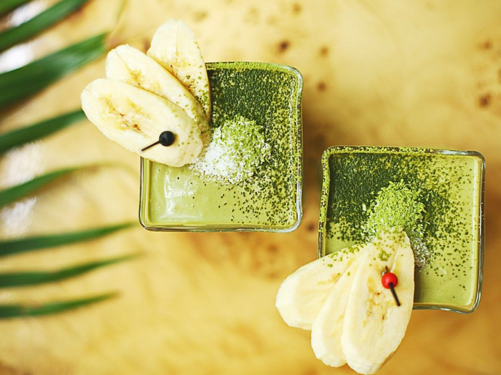 Δύο ποτήρια με πράσινο milkshake με διακόσμηση στο χείλος τους φέτες μπανάνας σε κίτρινο φόντο
