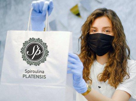 Γυναίκα με μαύρη ιατρική μάσκα στο πρόσωπο και μοβ γάντια μιας χρήσης κρατάει μία χάρτινη σακούλα αγορών με το λογότυπο Spiroulina PLATENSIS.