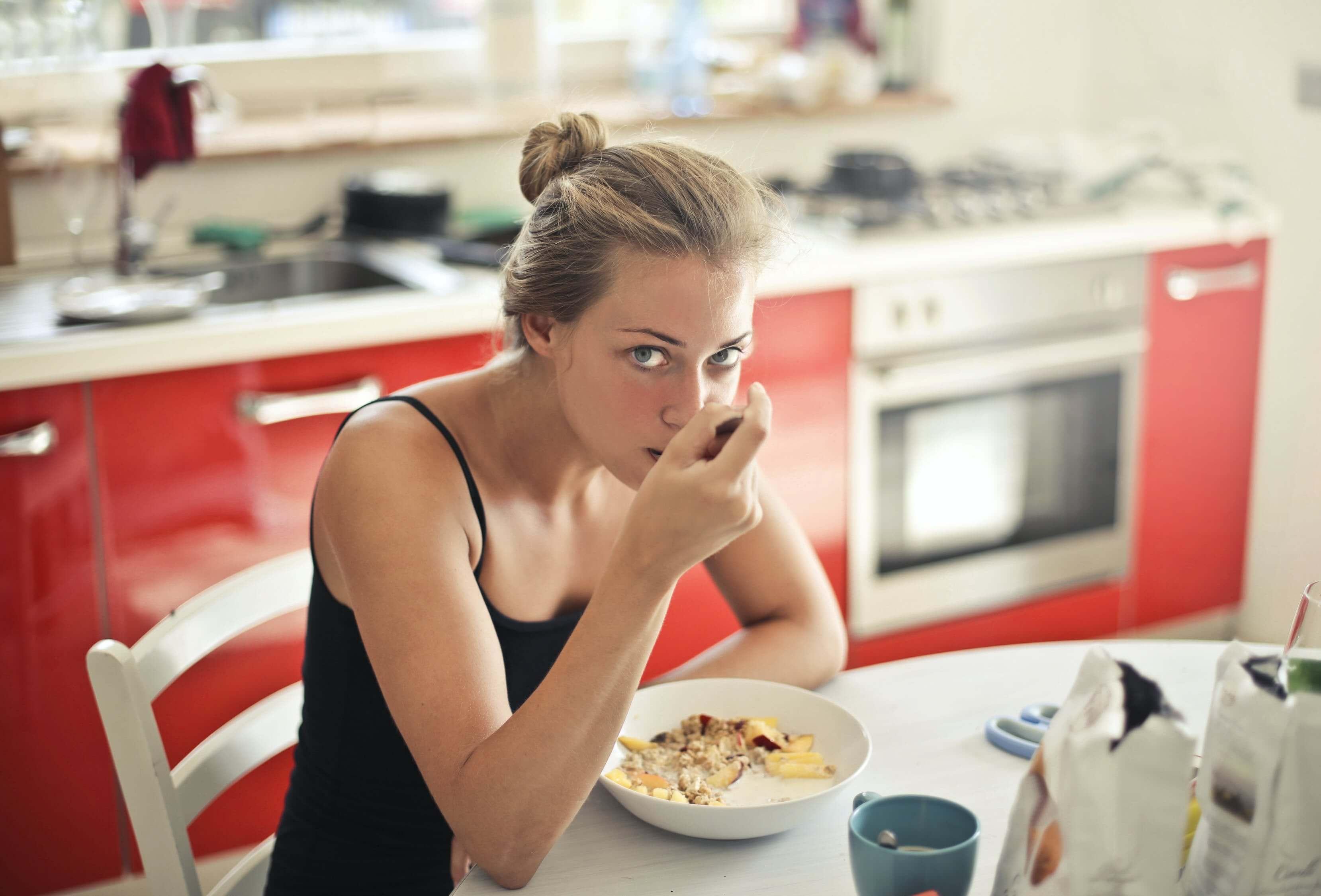 Νεαρή ξανθιά γυναίκα τρώει δημητριακά για πρωινό στο τραπέζι της κουζίνας