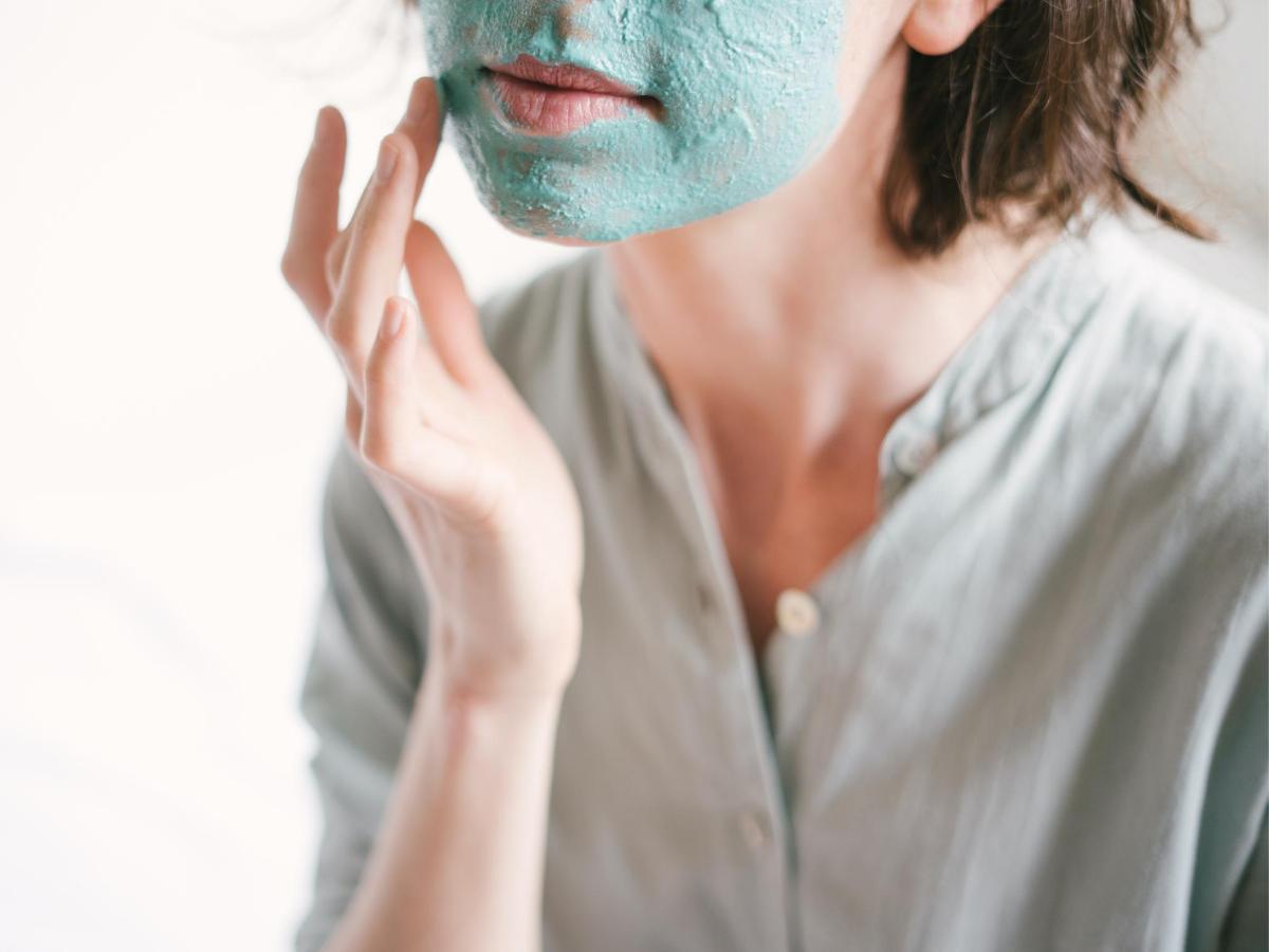 Νεαρή γυναίκα που εφαρμόζει μάσκα ομορφιάς στο πρόσωπο