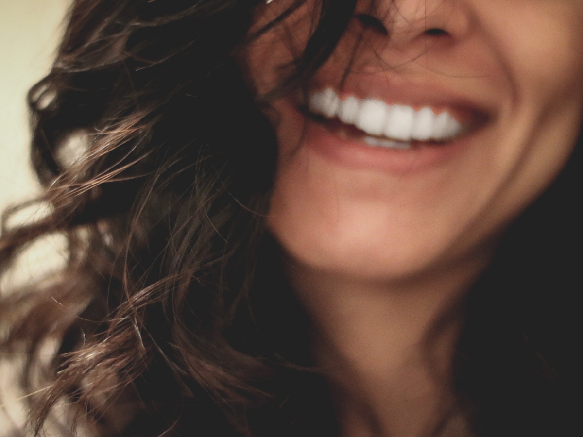 Γυναίκα με λαμπερά καστανά μαλλιά που χαμογελάει