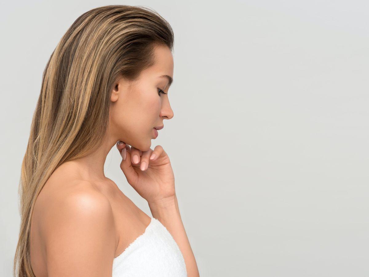 Γυναίκα με καστανά μαλλιά που φοράει λευκή πετσέτα στο σώμα της