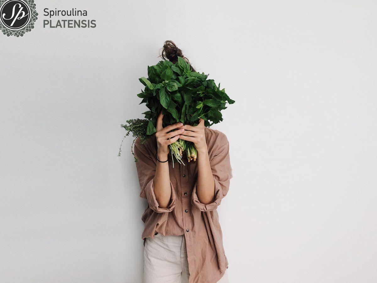 Νεαρή γυναίκα που κρατάει πράσινα λαχανικά και κρύβει το πρόσωπό της