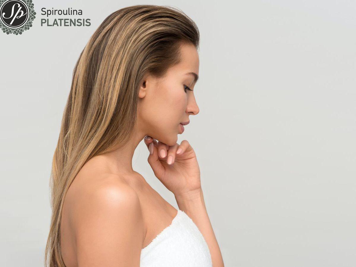 Νεαρή ξανθιά γυναίκα με λευκή πετσέτα και υγιές δέρμα
