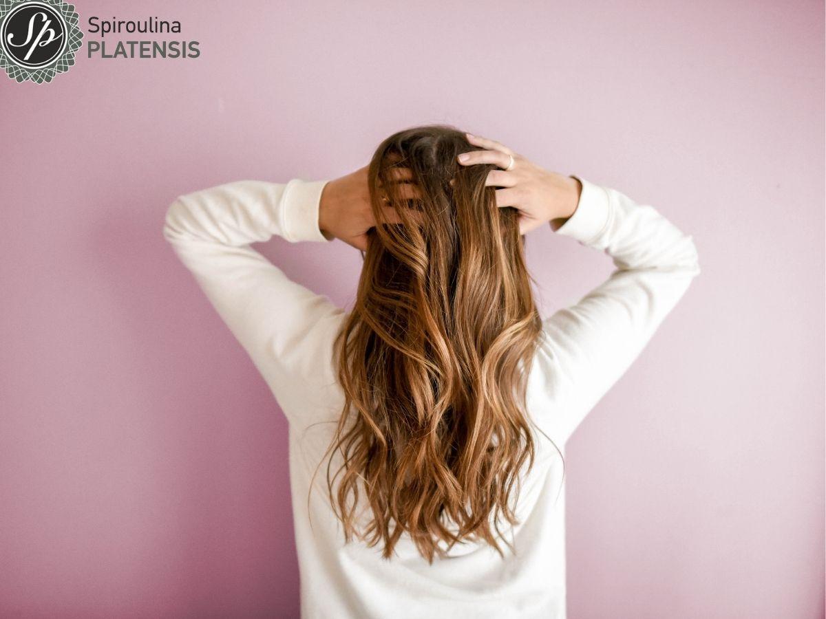 Γυναίκα με μακριά ξανθά μαλλιά σε ροζ φόντο με λευκό φούτερ
