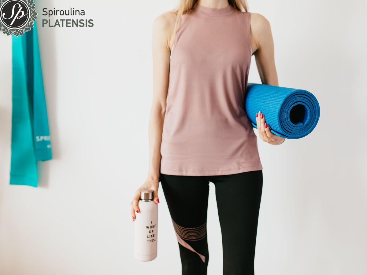 Νεαρή γυναίκα με αθλητικά ρούχα που κρατάει μπλε στρώμα γυμναστικής και ένα μπουκάλι