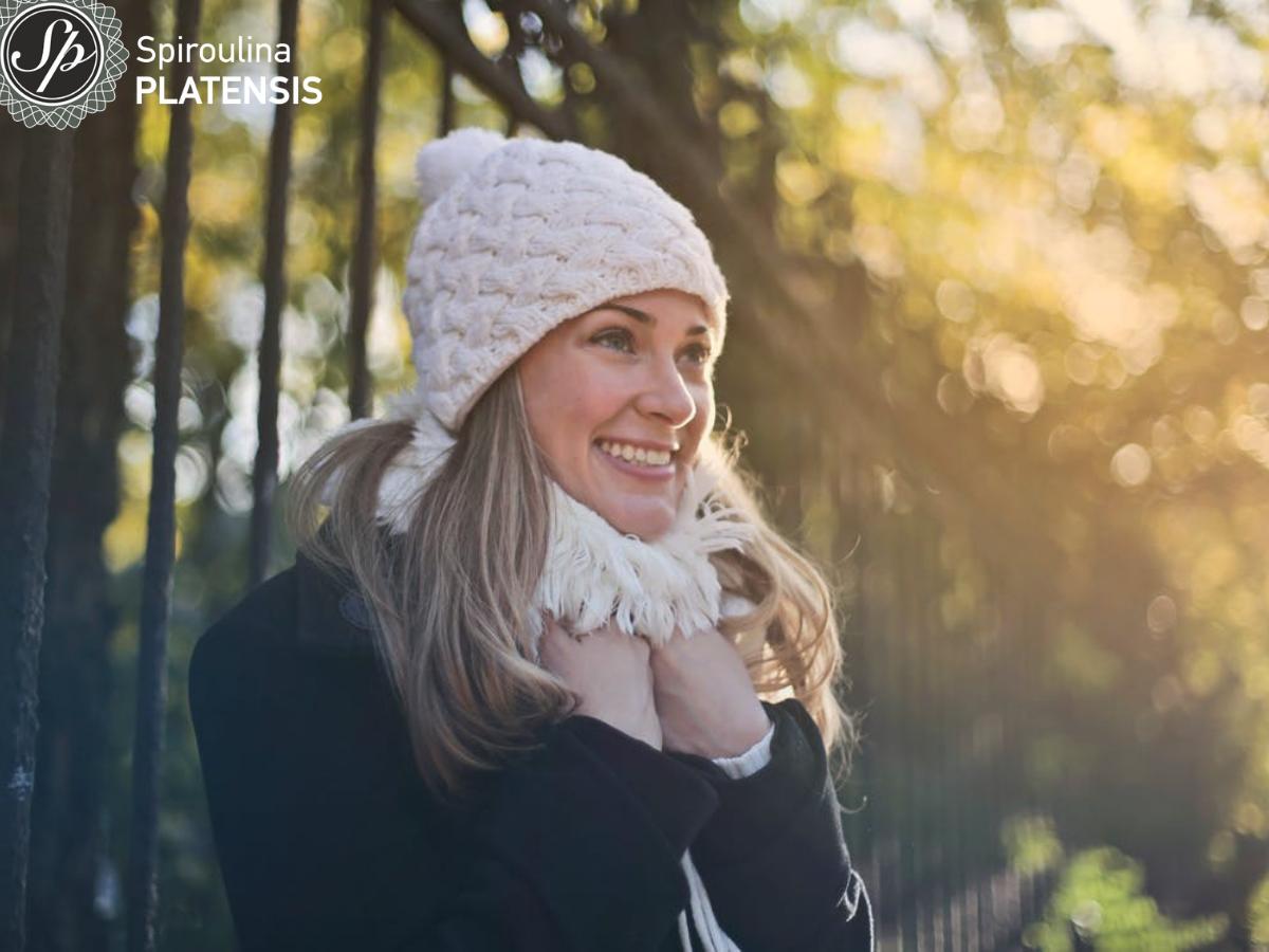 Νεαρή γυναίκα με σκουφί και κασκόλ σε δάσος χαμογελάει