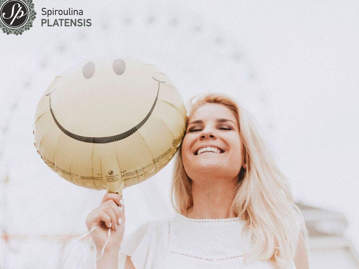Ξανθιά γυναίκα που χαμογελάει κρατώντας ένα μπαλόνι με σκίτσο με χαρούμενη φάτσα