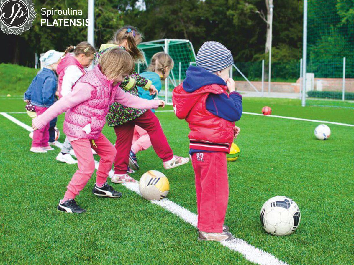 Μικρά αγόρια και κορίτσια παίζουν σε ένα γήπεδο ποδόσφαιρο