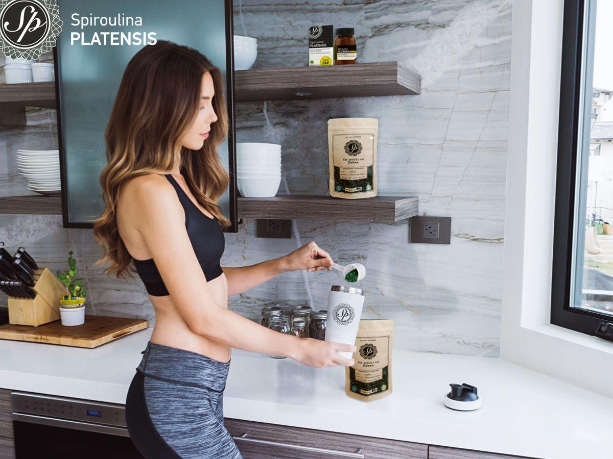 Νεαρή γυναίκα με αθλητικό ντύσιμο ετοιμάζει smoothie με Σπιρουλίνα flakes