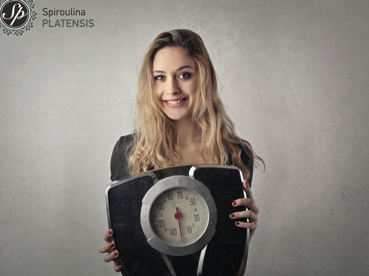 Νεαρή ξανθιά κοπέλα που κρατάει μία ζυγαριά