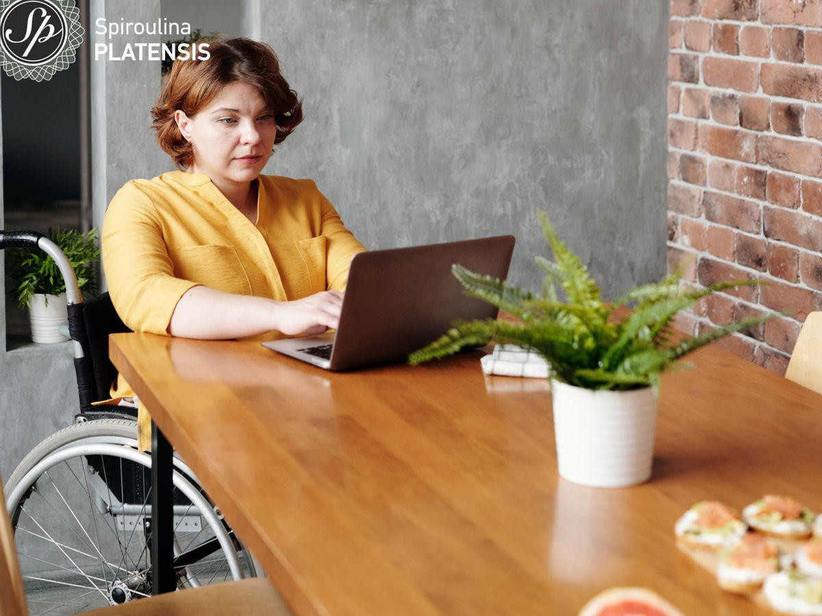 Γυναίκα σε αναπηρικό αμαξίδιο που δουλεύει σε υπολογιστή από το σπίτι της