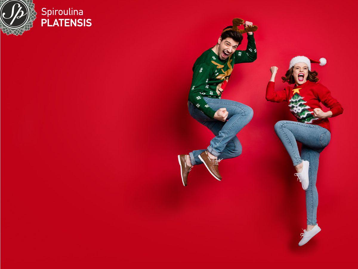Άνδρας & γυναίακ με χριστουγεννιάτικα ρούχα που πετάνε ψηλά μπροστά από κόκκινο φόντο