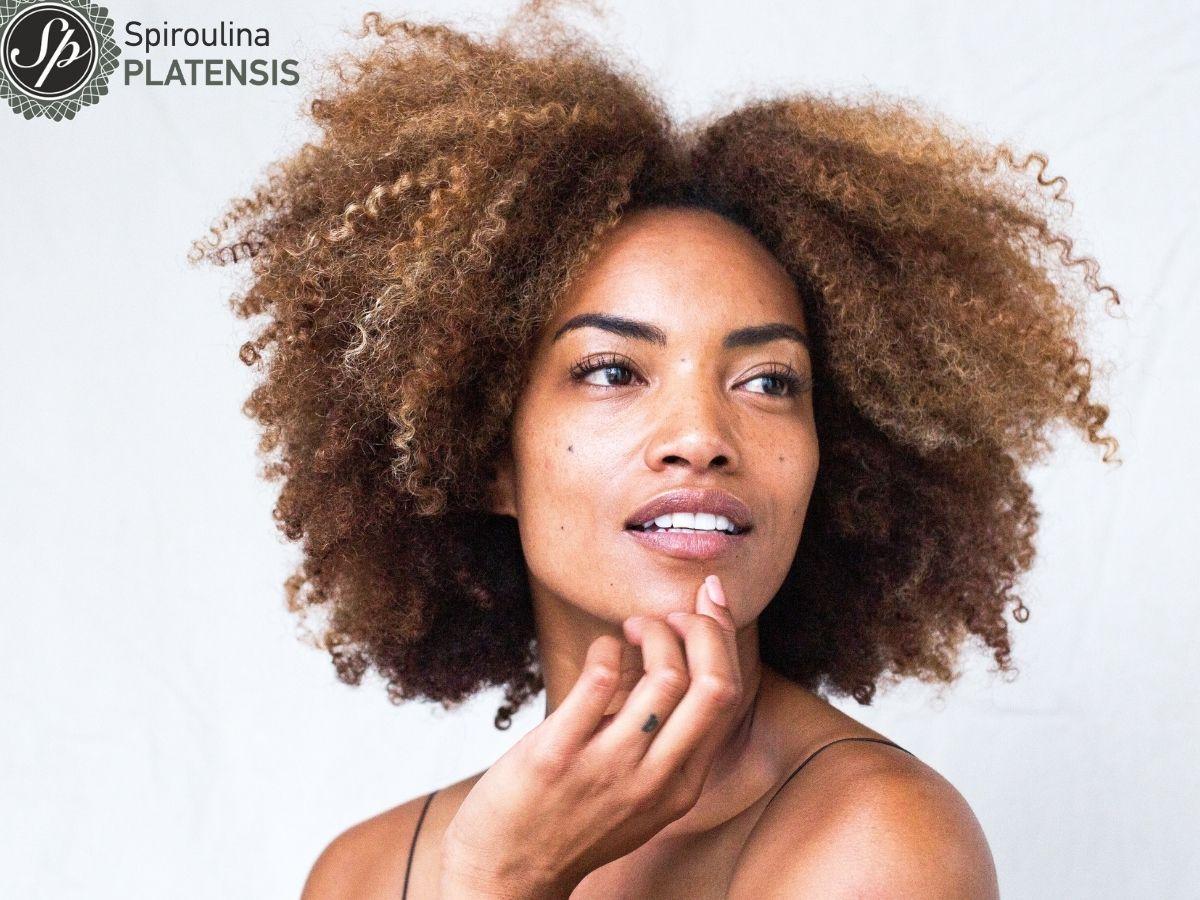 Όμορφη γυναίκα με λαμπερό πρόσωπο και πλούσια κατσαρά καστανά μαλλιά