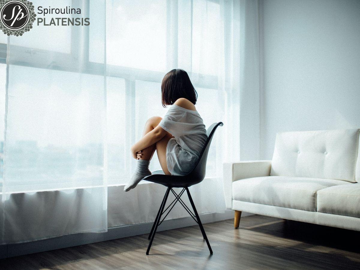 Κοπέλα που κάθεται πίσω από ένα παράθυρο με λευκή κουρτίνα