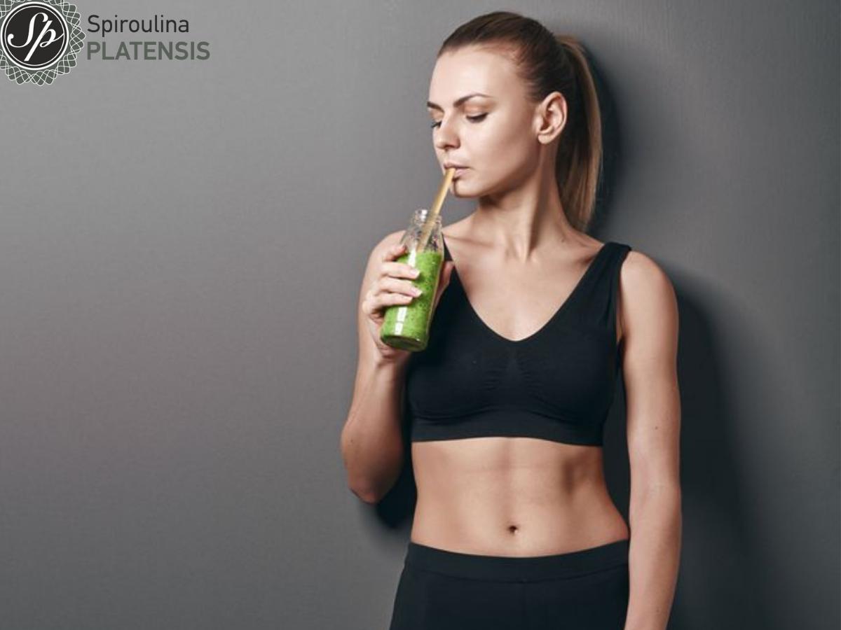 κοπέλα με αθήτικό ντύσιμο πίνει πράσιμο smoothie με spiroulina platensis και bamboo καλαμάκι