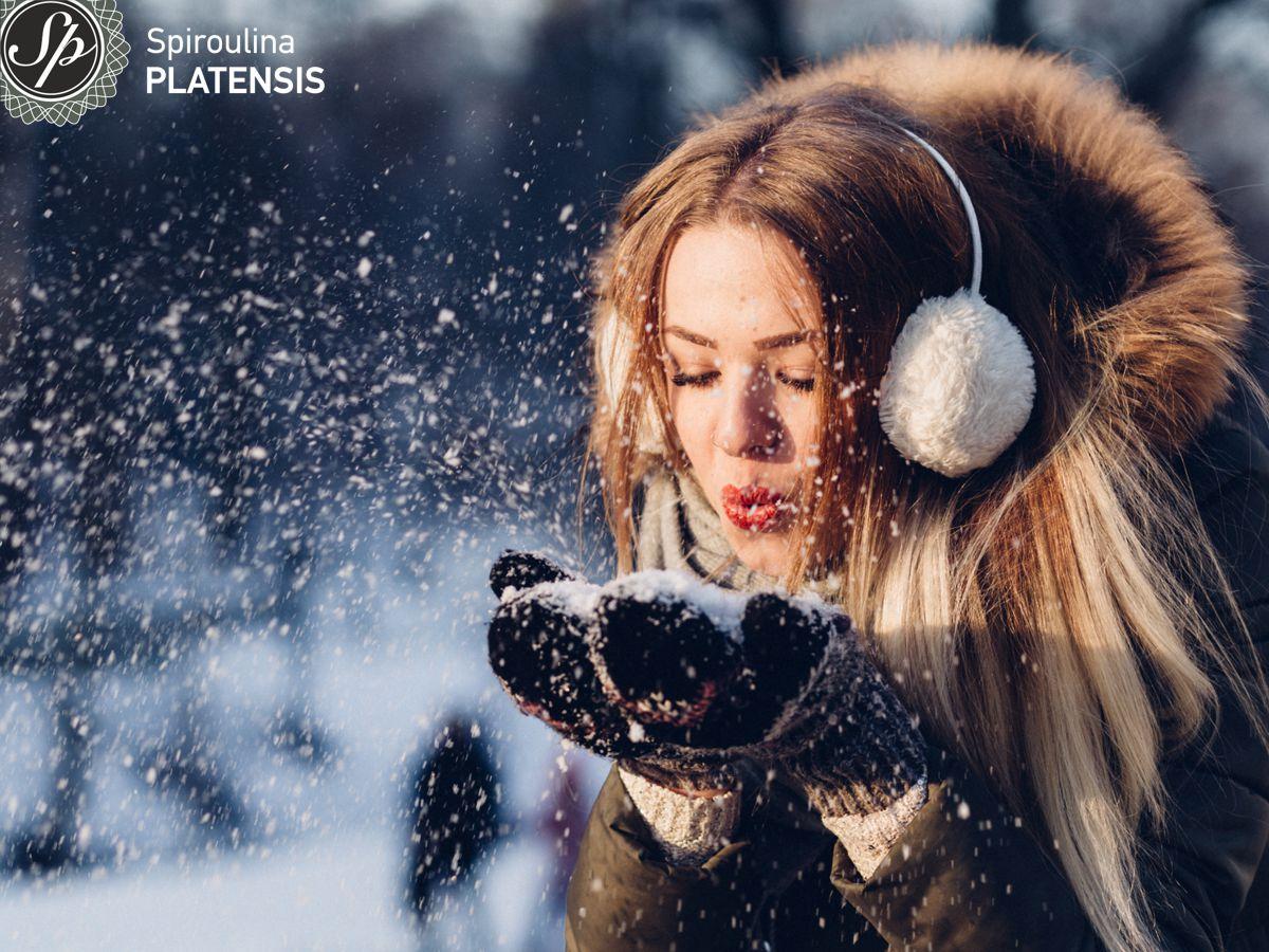 Νεαρή γυναίκα με ξανθά μαλλιά που κρατάει χιόνι