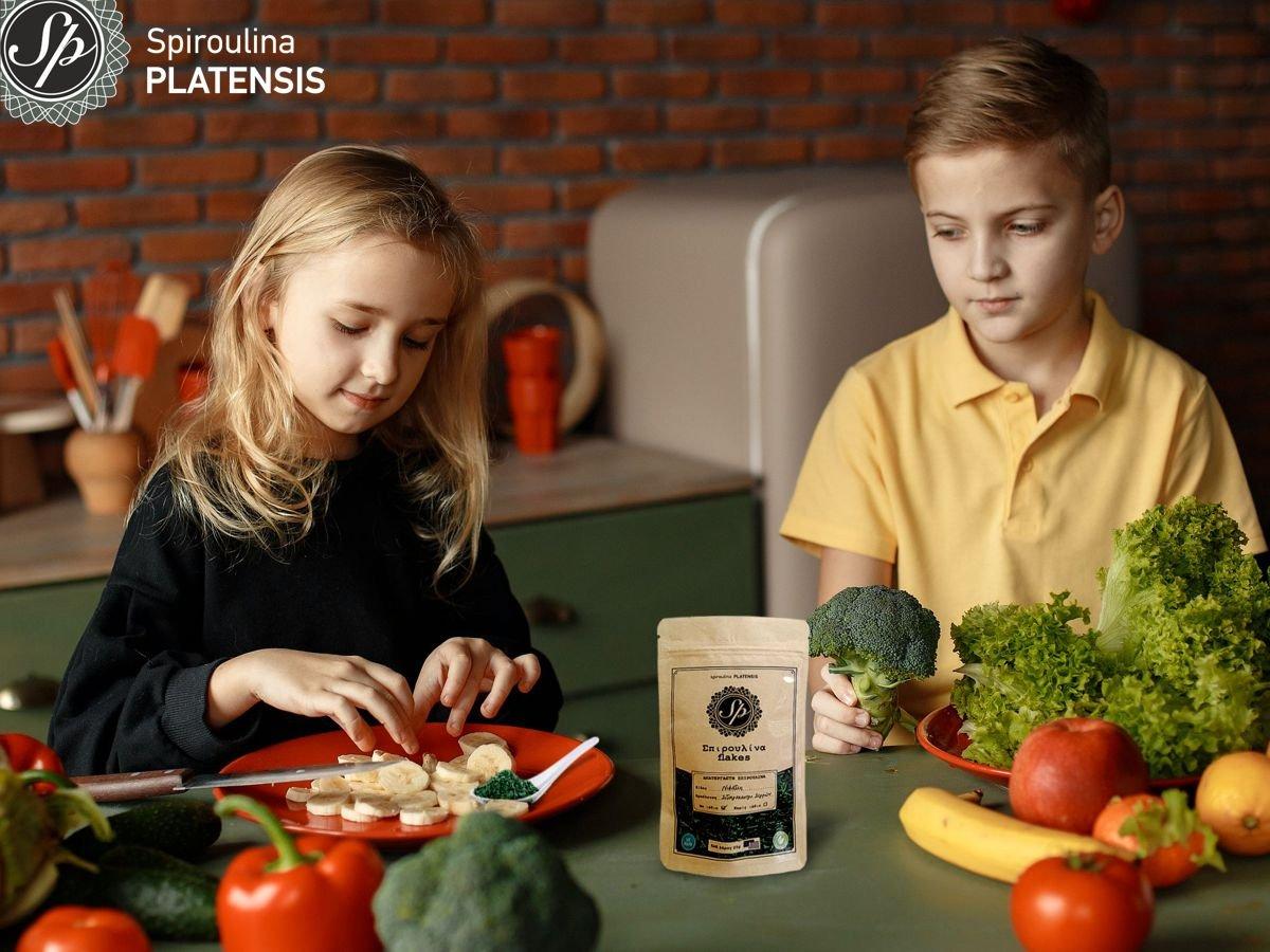 Δύο παιδιά, ένα αγόρι κι ένα κορίτσι που κάθονται πίσω από ένα τραπέζι που περιέχει πολλά φρούτα & λαχανικά & Σπιρουλίνα flakes