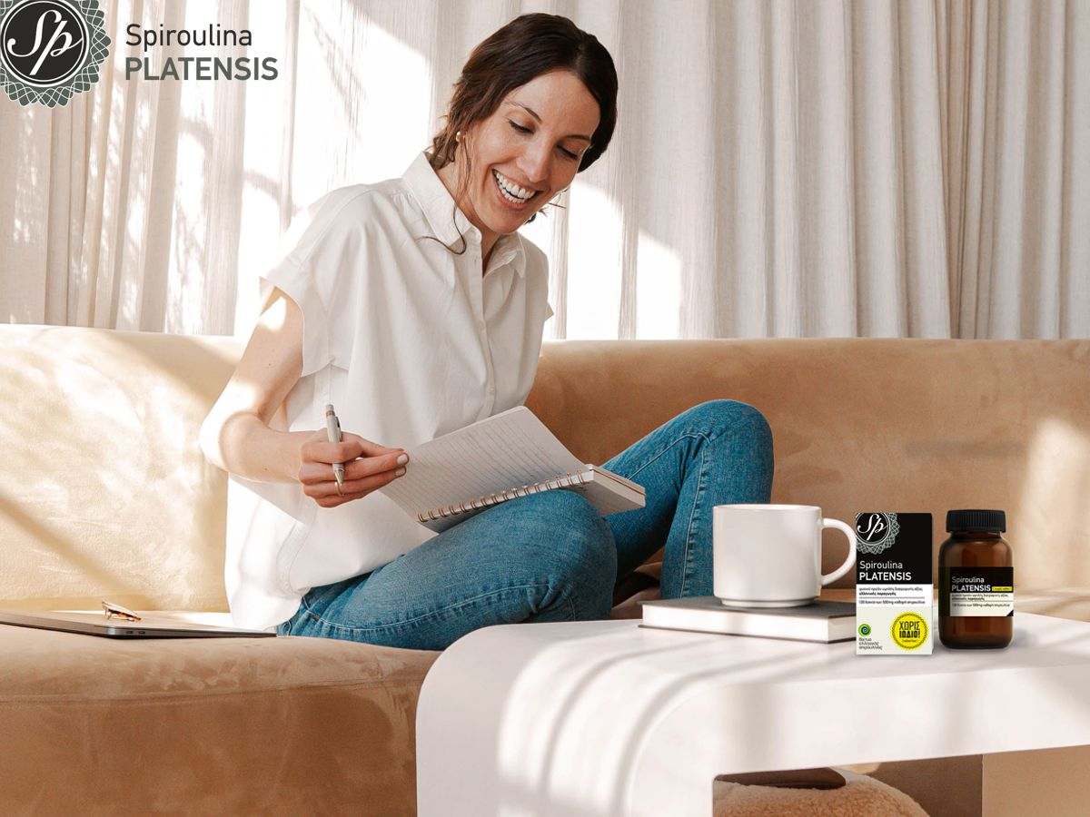 Χαμογελαστή γυναίκα με λευκό πουκάμισο και τζιν δουλεύει από το σπίτι