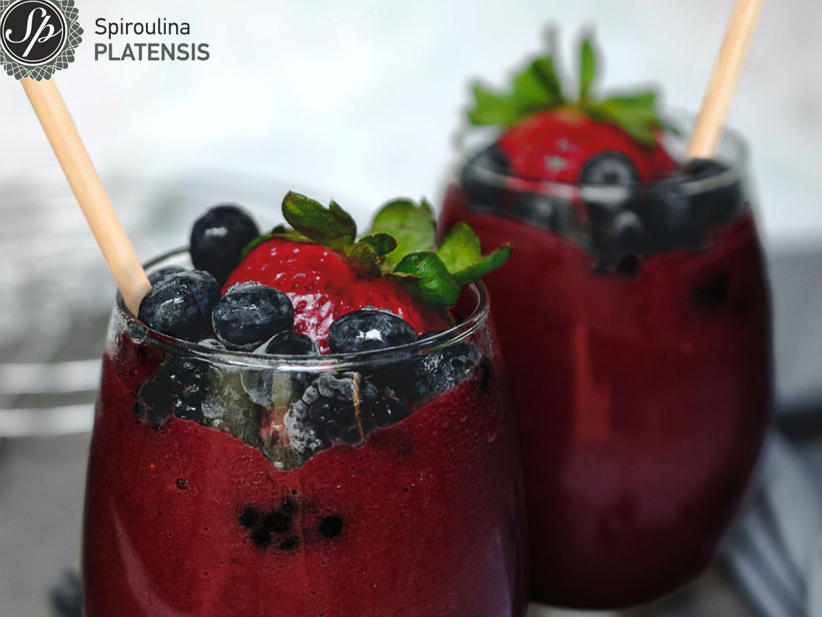 Κόκκινο smoothie με Spiroulina PLATENSIS σε γυάλινο ποτήρι και bamboo καλαμάκι